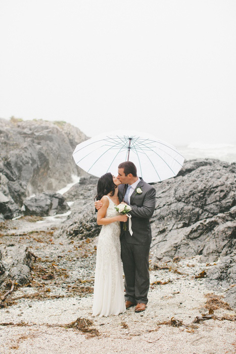 bride and groom on the beach in the rain