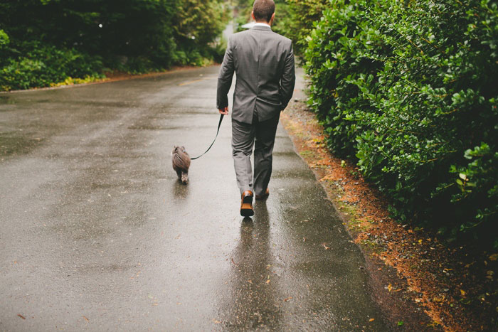 groom walking his dog