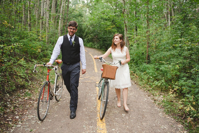 bride and groom walking down the road with bikes