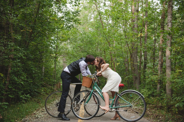 bride and groom kissing on bikes