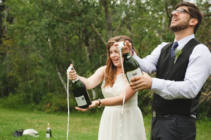 bride and groom popping champagne bottles