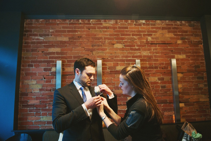 groom pinning on boutonniere