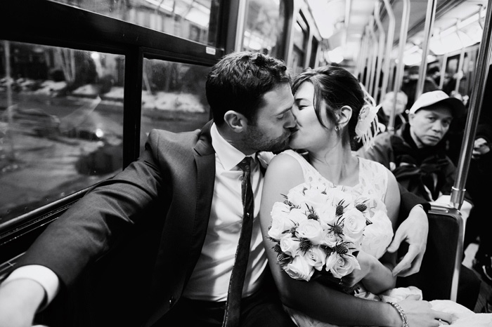 bride and groom kissing on the streetcar