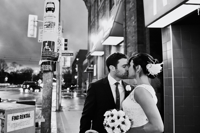 bride and groom kissing on the street at night