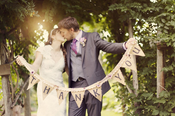 bride and groom with thank you bunting