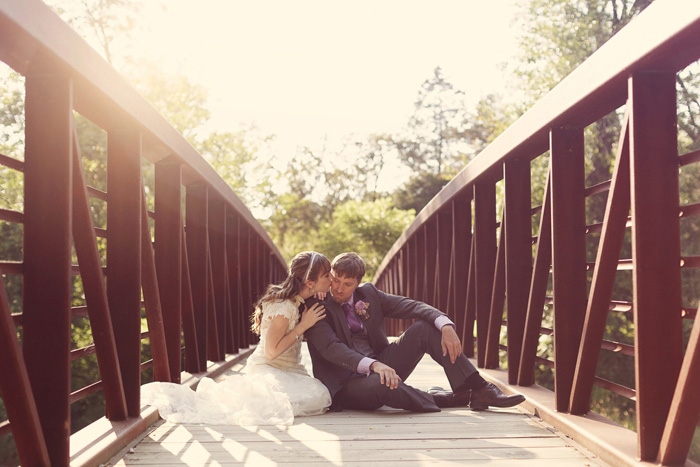 bride and groom sitting on wooden bridge