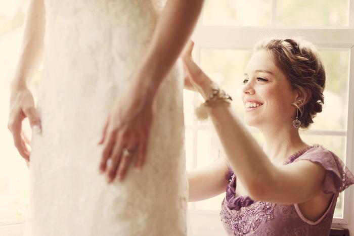 bridesmaid buttoning bride's dress