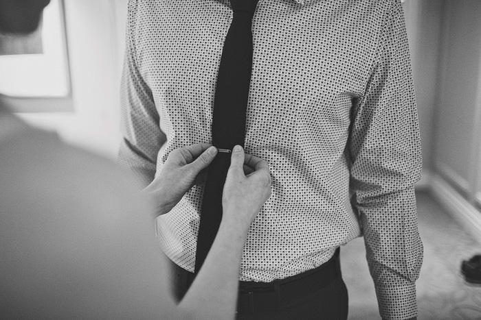bride clipping groom's tie