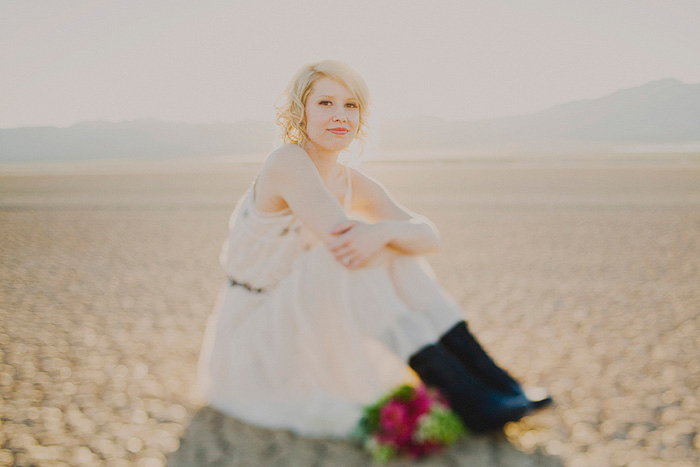 bride sitting in dry lake bed