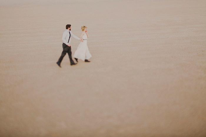 bride and groom walking through the desert