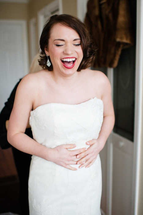 bride laughing while getting dressed