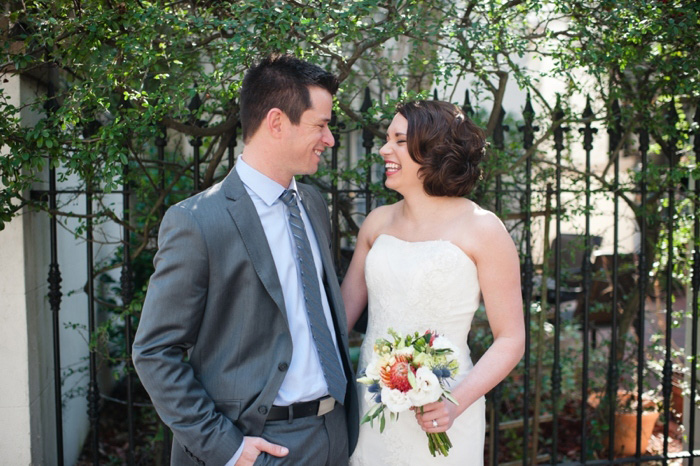 bride and groom in front of wrought iron fence
