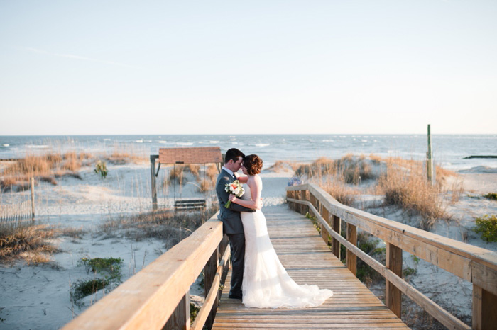 bride and groom kissing on the boardwalk