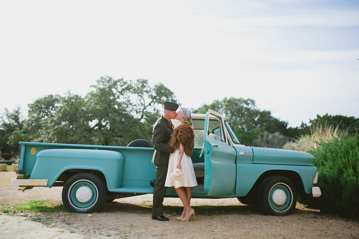 bride and groom kissing in front of vintage pick-up truck