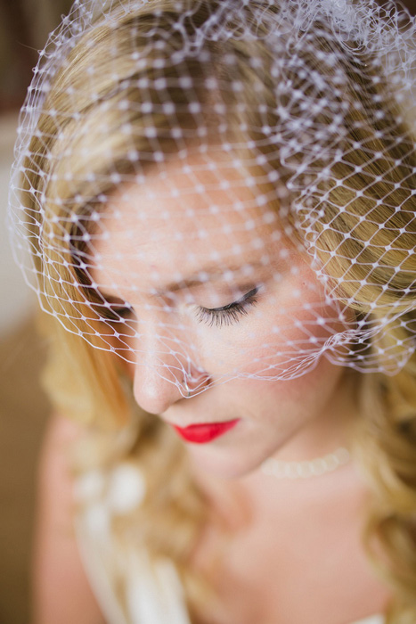 bride with red lip and birdcage veil