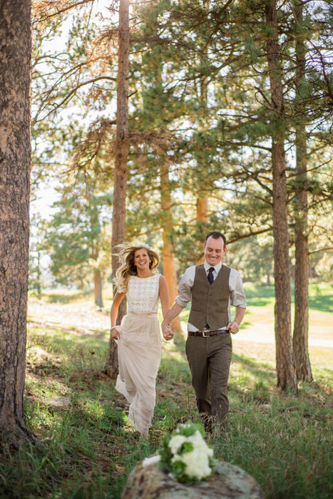 bride and groom running through the woods