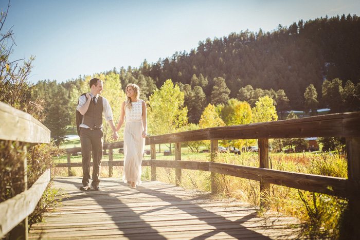 bride and groom walking across wooden bridge