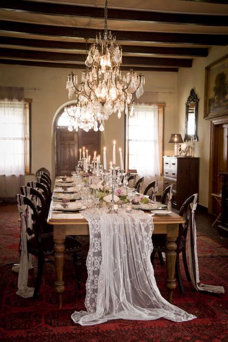 Bàn ăn mang đậm chất xa xỉ của thời kì trước với bàn gỗ tối màu và khăn bàn bằng voan.