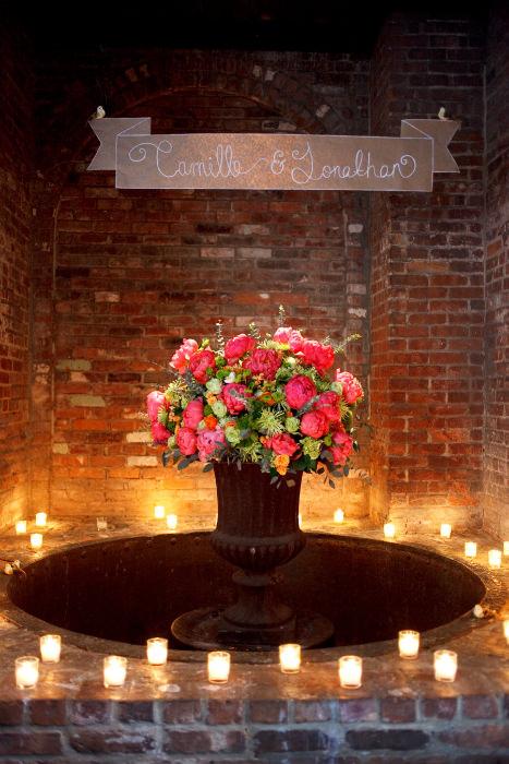 Nến và hoa làm nổi bật bảng thông báo tên cô dâu- chú rể trong đám cưới.