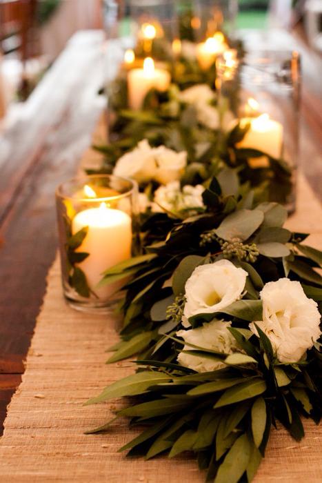 Nến cùng hoa và lá là điểm nhấn cho những một bàn tiệc dài.