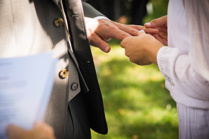 bride putting ring n groom's finger