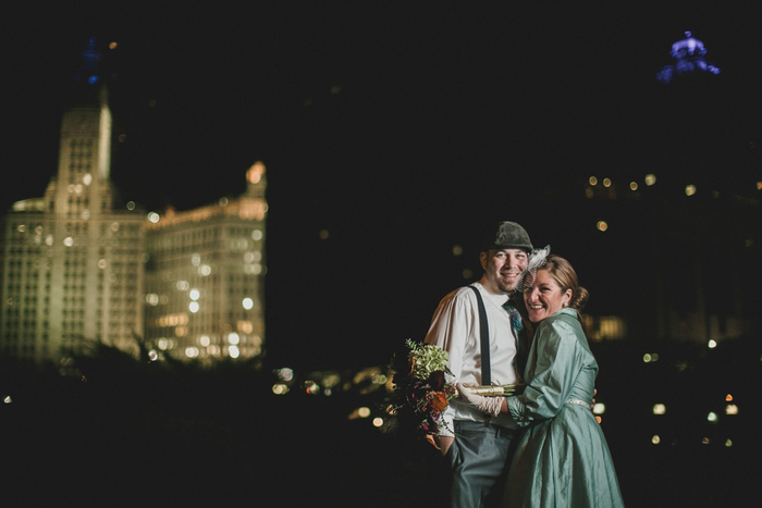 bride and groom in front of night time cityscape