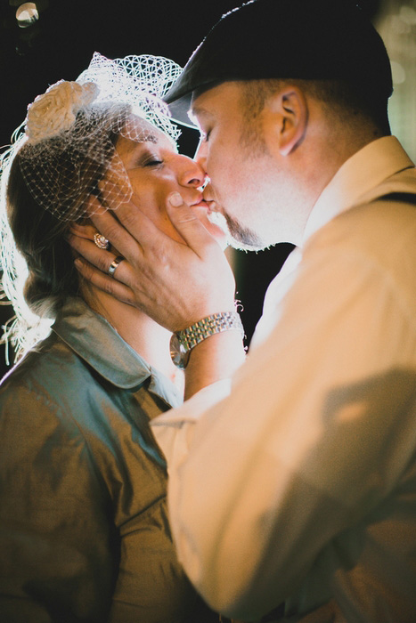 bride and groom kiss at night