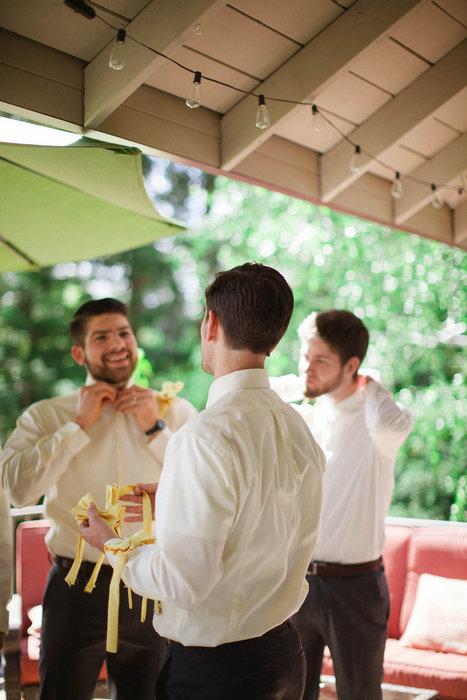groomsmen putting on bow ties