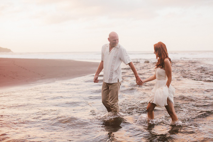 bride and groom walking in the surf