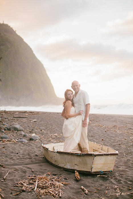 bride and groom standing in a wooden row boat