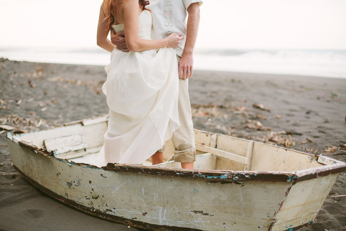 bride and groom standing in wooden boat