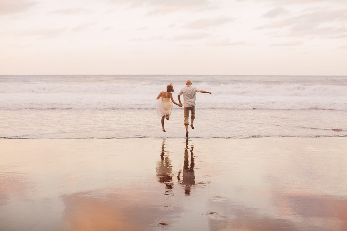bride and groom skipping along beach in Hawaii