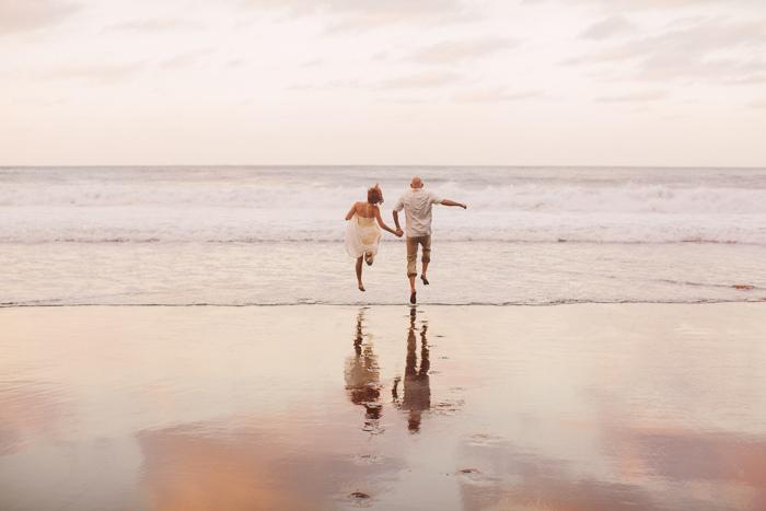 bride and groom skipping along beach in Hawaii