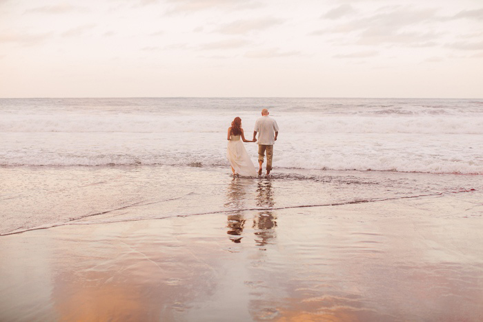 bride and groom walking into the ocean