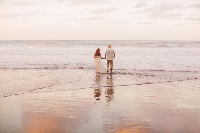 bride and groom walking into the ocean