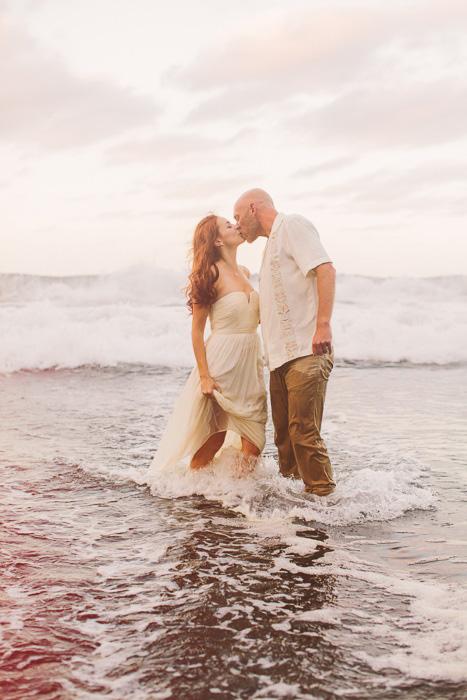 bride and groom kissing in the ocean