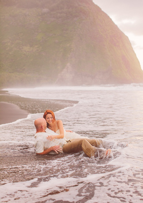 bride and groom lying in the surf