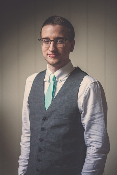 groom in vest and aqua tie