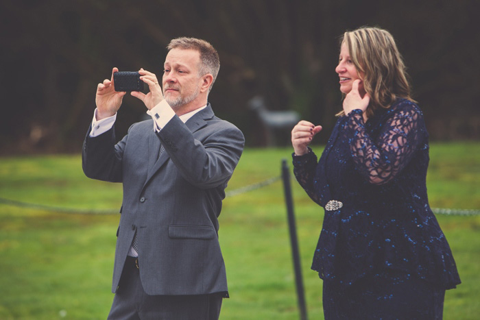 mom and dad taking photos at wedding