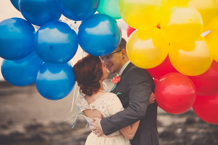bride and groom kissing beneath balloons