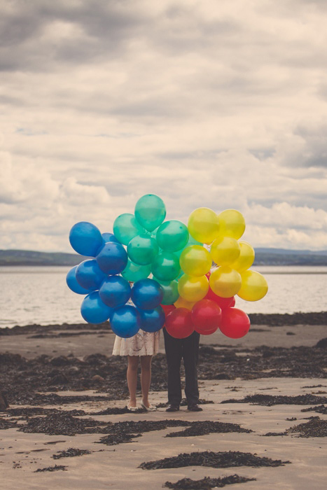 bride and groom on beach with balloons