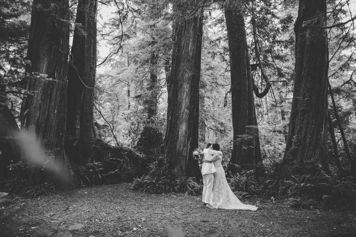 brides hugging in the woods