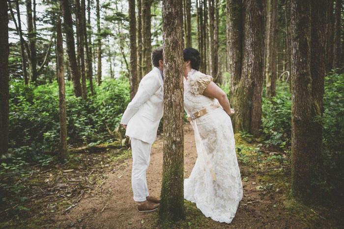 brides kissing behind tree
