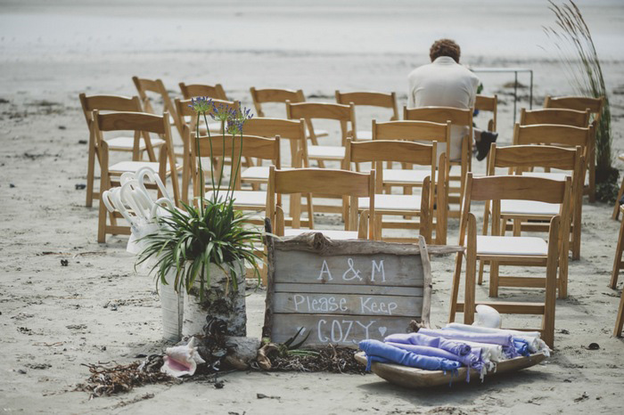 wooden folding chairs set up on the beach for wedding ceremony