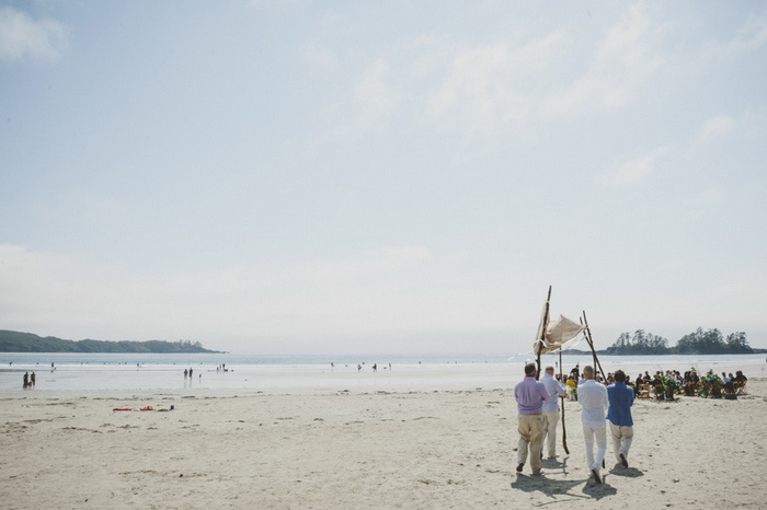 people carrying wedding canopy down the beach