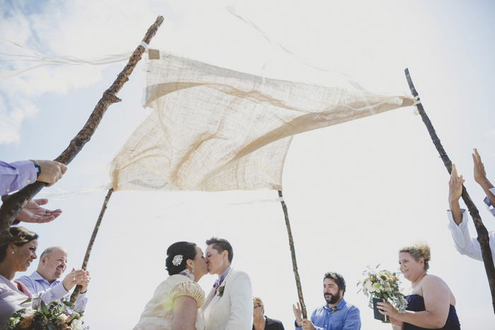 brides kissing under wedding canopy