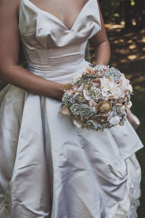 Bó hoa cầm tay cô dâu thêm phần quý phái với những chi tiết đính đá cầu kì.