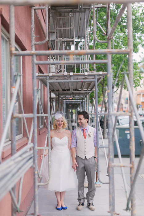 bride and groom under scaffolding