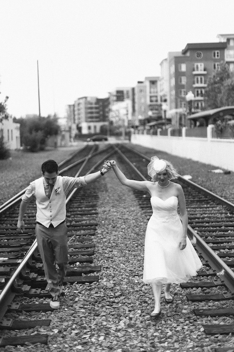 bride and groom walking on train tracks
