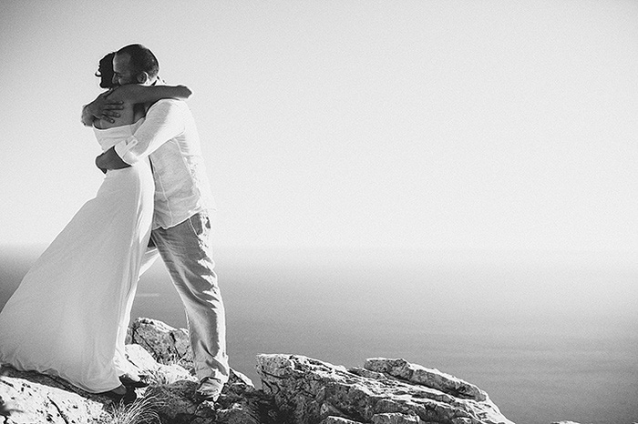 bride and groom hugging on croatian cliff